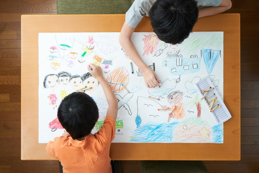 大きな紙にお絵描きする兄弟